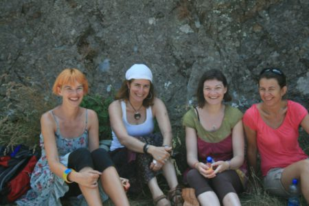 Four women resting in the shade having hikes in the sun