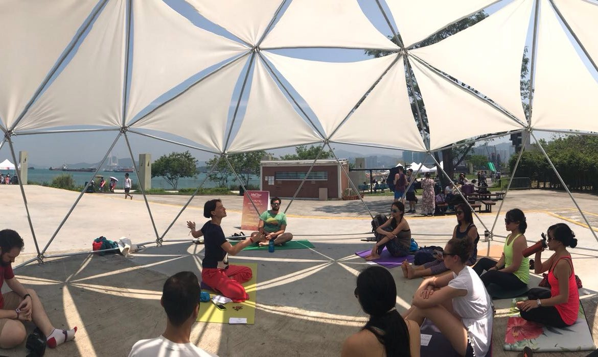 Workshop participants sit under white canvas dome.