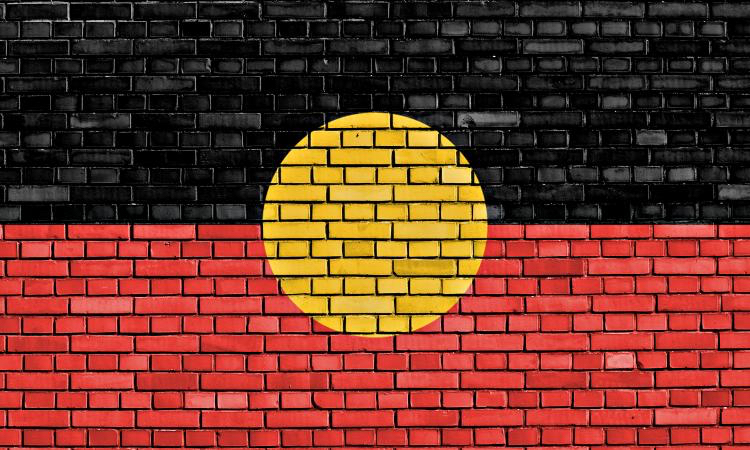 Brick wall painted with Aboriginal flag, top half is black, bottom half is red with a yellow sun in the centre.