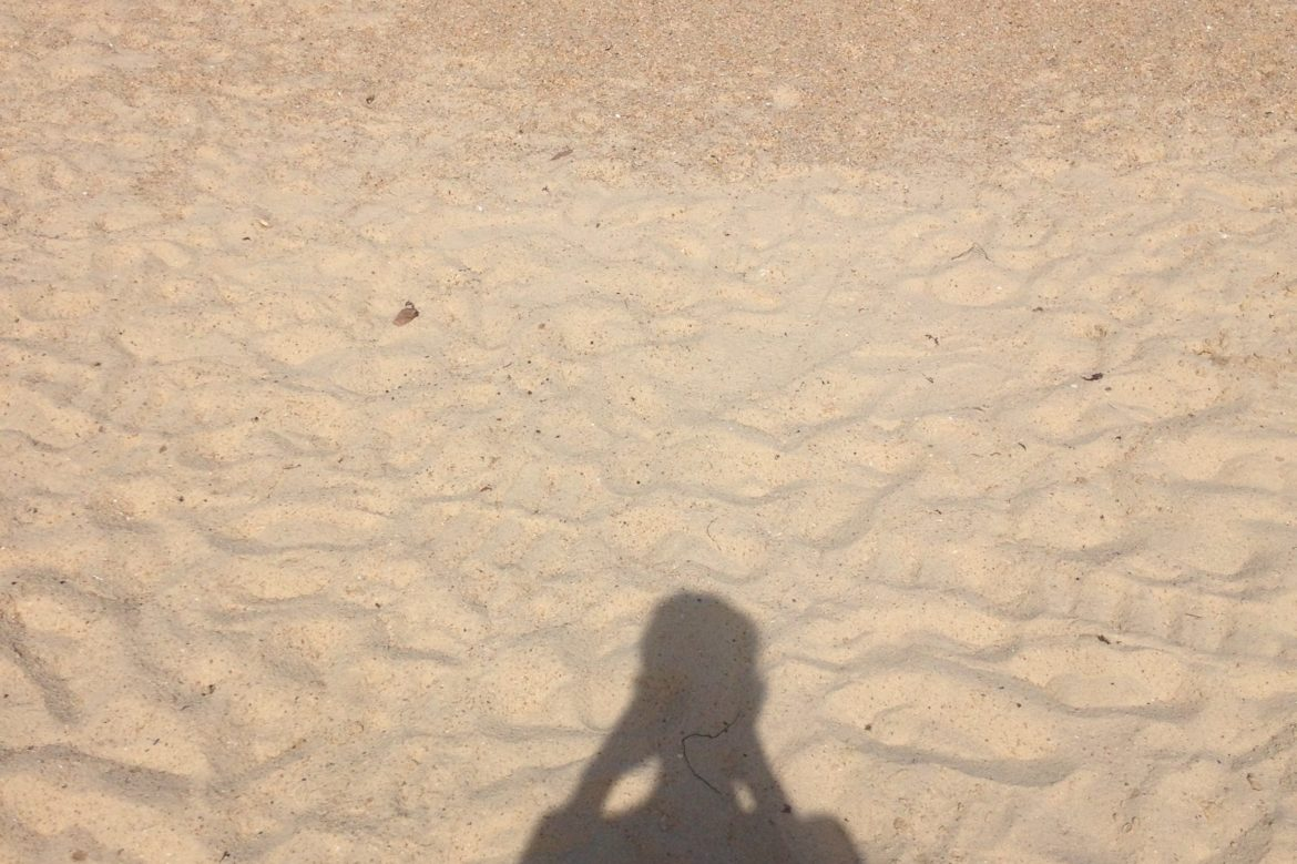 shadow of human head and torso on sand.