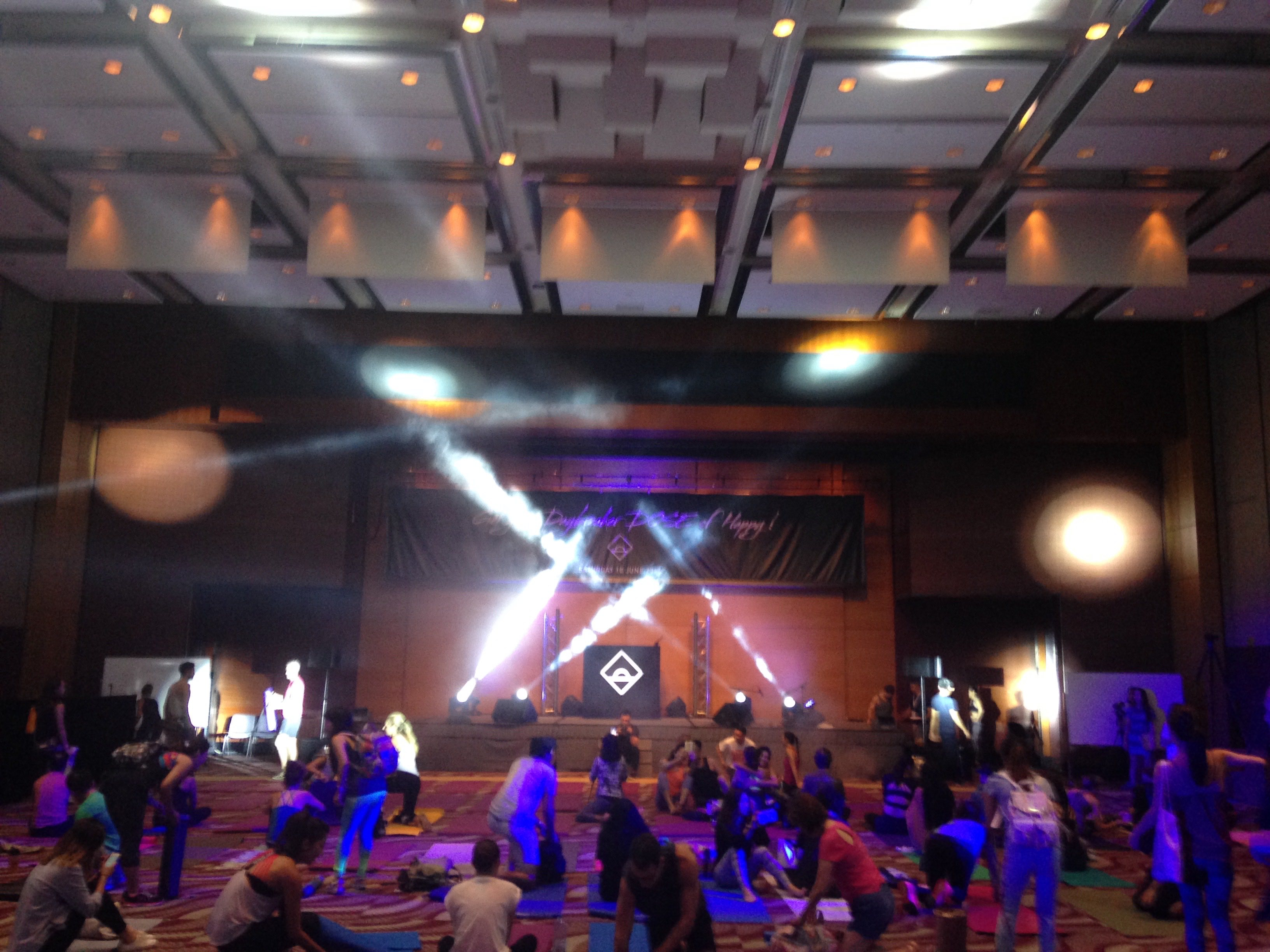 Large hall with people setting up mats amid lazer beams.